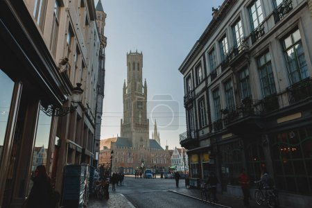 Photo for BRUGGE, BELGIUM - NOVEMBER 02, 2016: low angle view of famous belfort tower and people on street in brugge, belgium - Royalty Free Image