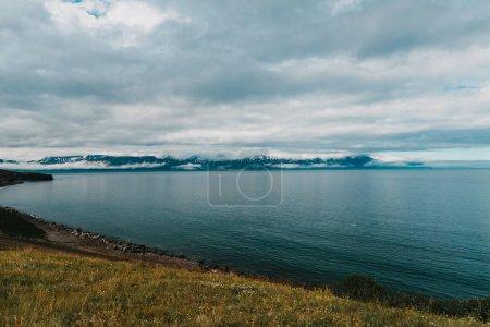 Photo pour Majestueux littoral glaciaire avec montagnes rocheuses et ciel nuageux - image libre de droit