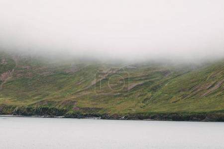 Photo pour Magnifique littoral de glace avec des collines verdoyantes dans le brouillard, nord de l'iceland - image libre de droit