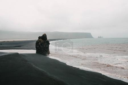 Beautiful seacoast with black sand and cliff at fo...