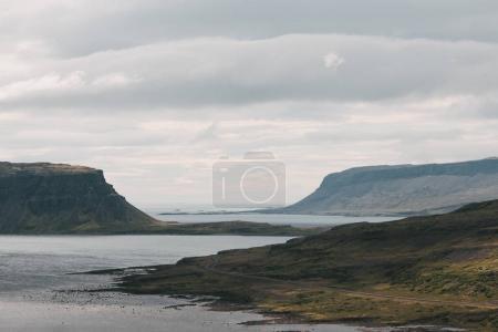 Photo pour Magnifique côte islandaise collines et un port au temps nuageux - image libre de droit