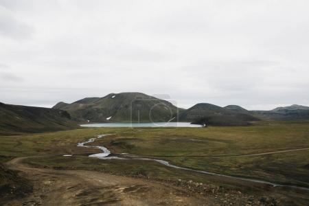 Photo pour Petite rivière de l'eau de fonte, collines rocheuses avec végétation verte et lac en iceland - image libre de droit