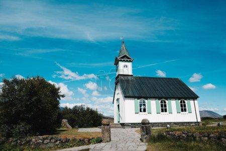 Photo pour Architecture de la belle église traditionnelle et de vieux mur de pierre à jour ensoleillé, Pingvallakirkja, Islande - image libre de droit