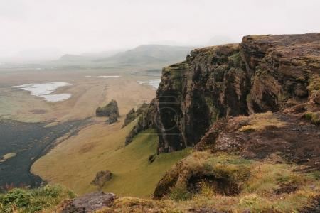 Photo for Majestic landscape with rocky mountains and grassy plain with snow in iceland - Royalty Free Image