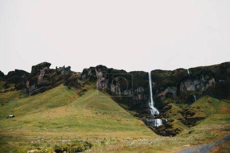 Photo pour Belle vue panoramique sur la cascade, les rochers et les pentes vertes en iceland - image libre de droit