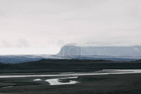 Photo pour Beau paysage glaciaire avec sable volcanique noir dans la neige et montagnes rocheuses dans le brouillard - image libre de droit