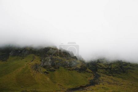 Photo pour Les collines rocheuses majestueuses recouvert de mousse verte dans le brouillard, Islande - image libre de droit