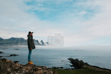 Photo for Side view of young man standing on rock and looking at beautiful seascape, iceland - Royalty Free Image