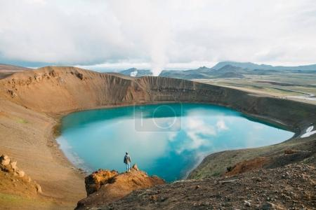 Photo for Back view of man looking at majestic volcanic lake in iceland, krafla, lake viti - Royalty Free Image