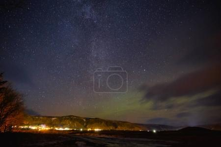 Photo for Illuminated buildings and beautiful starry sky with northern lights in iceland - Royalty Free Image