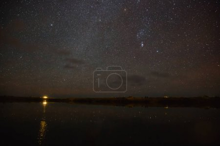 Photo for Illuminated building reflected in water and majestic starry sky at night, iceland - Royalty Free Image