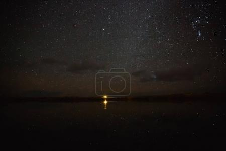 Photo for Illuminated building reflected in water and spectacular starry sky at night, iceland - Royalty Free Image