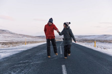 Photo for Happy young couple holding hands and walking on asphalt road in iceland - Royalty Free Image