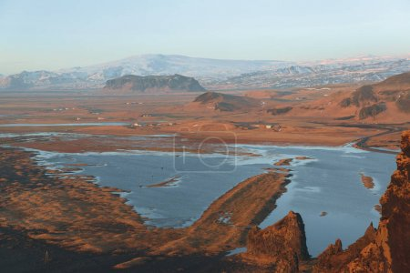 beautiful icelandic landscape with rocky hills, water and buildings