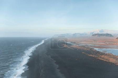 Photo for Beautiful wavy sea and shore with mountains on horizon, vik dyrholaey, reynisfjara beach, iceland - Royalty Free Image