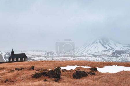 Foto de Hermosa pequeña iglesia y montañas cubiertas de nieve en Budir, Península de Snaefellsnes, Islandia - Imagen libre de derechos