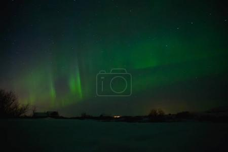Photo for Houses under sky with spectacular aurora borealis in iceland - Royalty Free Image