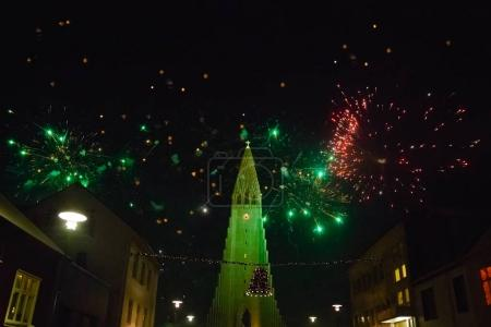 Photo for REYKJAVIK, ICELAND - 03 JANUARY, 2017: beautiful architecture and colorful fireworks in night sky at iceland - Royalty Free Image