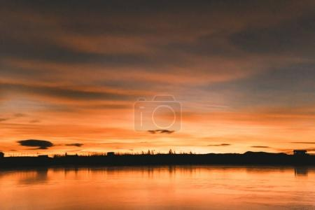 Photo for Scenic view of skyline with trees and buildings reflected in water at sunset, iceland - Royalty Free Image