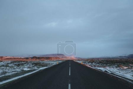 empty asphalt road and snow-covered icelandic landscape at sunrise