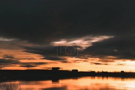 Photo pour Belle skyline avec les arbres et les bâtiments reflète dans l'eau au coucher du soleil, Islande - image libre de droit