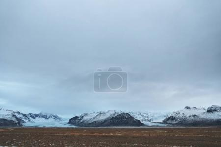 Photo for Beautiful scenic view of snow-covered rocky mountains and cloudy sky, iceland - Royalty Free Image