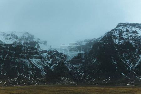 Photo pour Neige sur de belles montagnes rocheuses dans le brouillard, glacier jokulsarlon, iceland - image libre de droit