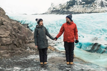 Photo for Beautiful young couple holding hands and smiling each other while standing near Svinafellsjokull Glacier, Iceland - Royalty Free Image