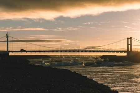 Photo for Car on bridge above river with icebergs at sunset, iceland - Royalty Free Image