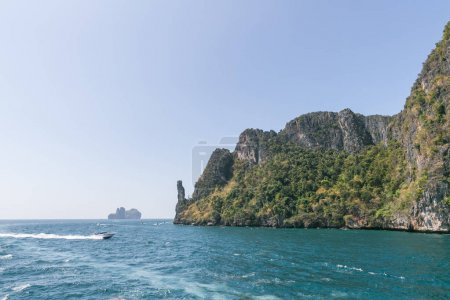 Photo for Scenic view of rocky formations covered with green plants, blue sky and ocean, phi phi islands - Royalty Free Image