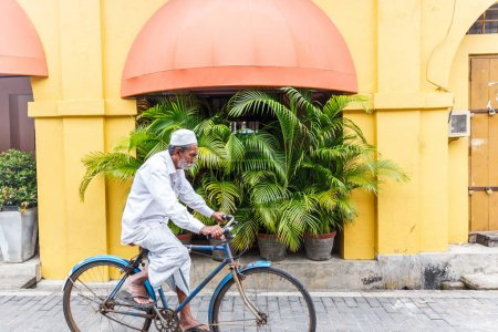 Photo for SRI LANKA, GALLE FORT - JAN 17, 2017: senior asian man riding bicycle on street, Asia - Royalty Free Image
