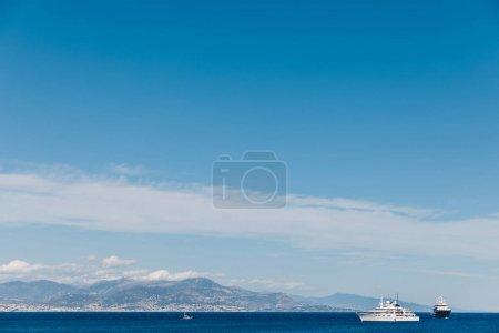 Photo pour Navires, flottant dans la mer par une journée ensoleillée avec les montagnes en arrière-plan, Antibes, France - image libre de droit