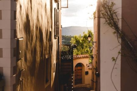 narrow street with ancient buildings at old town with sunset sky on background, Cannes, France