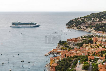 Photo for EZE, FRANCE - 17 SEPTEMBER 2017: ocean liner near harbour of old european city located on seashore, Eze, France - Royalty Free Image