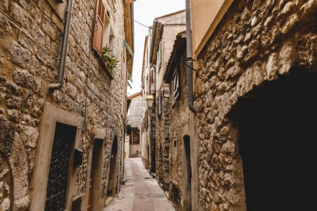 Photo for Narrow street with ancient stone buildings at old european town, Peille, France - Royalty Free Image