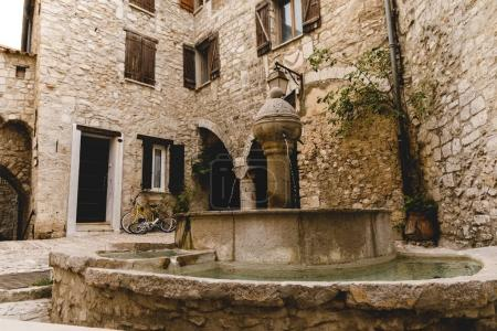 Photo for Atrium of ancient buildings at old town with beautiful fountain, Peille, France - Royalty Free Image