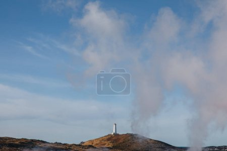 Photo pour Phare sur hill et vapeur de majestueux thermales géothermique en Islande, reykjanes, Gunnuhver Hot Springs - image libre de droit