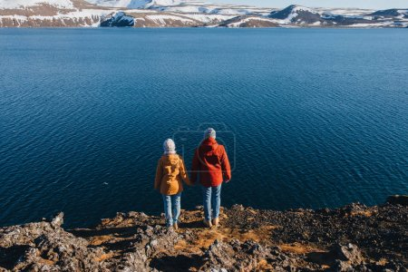 Photo for Back view of couple standing on rocky coast and looking at majestic icelandic landscape - Royalty Free Image