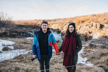 Happy young couple holding hands and smiling at camera while standing in beautiful icelandic landscape