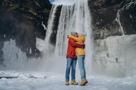 Photo for Beautiful young couple hugging and kissing near majestic skogafoss waterfall in iceland - Royalty Free Image