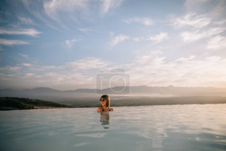 Photo for Beautiful young woman resting in natural pool at sunset, pamukkale, turkey - Royalty Free Image