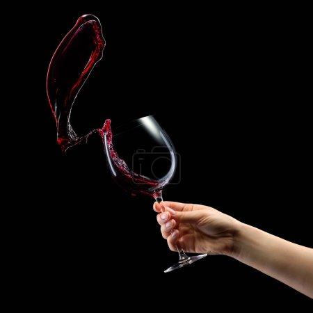 Foto de Mujer que sostiene el vaso de vino tinto con salpicaduras aisladas sobre fondo negro con carril de popa. - Imagen libre de derechos