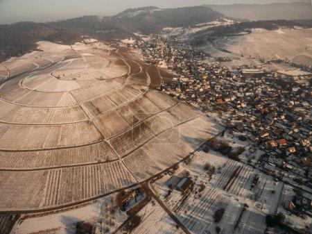 Photo pour Vue aérienne de magnifiques champs enneigés et maisons le matin d'hiver, Allemagne - image libre de droit
