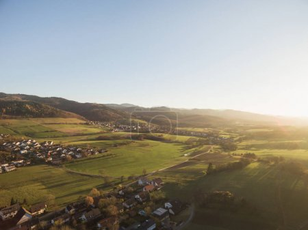 Photo for Aerial view of rooftops, houses and beautiful green hills with trees at sunlight, Germany - Royalty Free Image