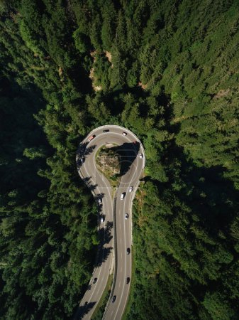 Photo for Aerial view of cars passing road around rock in forest - Royalty Free Image