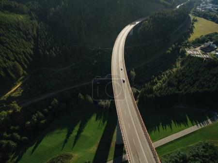 Photo for Aerial view of cars passing bridge over beautiful green forest - Royalty Free Image