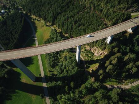 Photo for Aerial view of vehicle passing bridge over beautiful green forest - Royalty Free Image