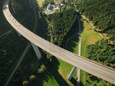 Photo for Aerial view of cars passing bridge over green forest - Royalty Free Image