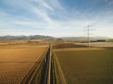 aerial view of electricity tower in agricultural fields on sunset, europe