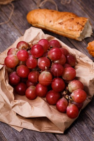A bunch of juicy large red grapes and fresh crispy wheaten bague
